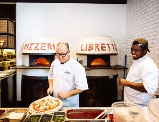 pizza chef and staff member picking up a pizza to put it in the pizza oven