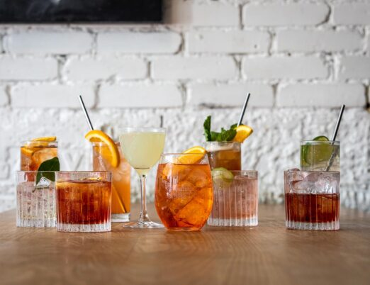 variety of iced cocktails in different shaped clear glasses on a wooden table