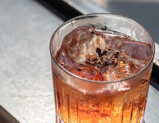 closeup of an iced cocktail with truffle shavings on top