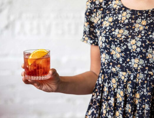 person holding a glass of aperol spritz