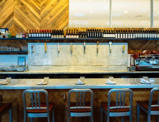 bar seating in front of beer spouts and a large espresso machine