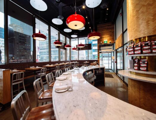 restaurant bar seating area with large windows with a view of downtown streets