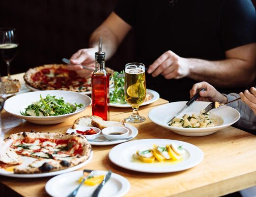 four people sitting at a restaurant table with pizzas and pasta dishes