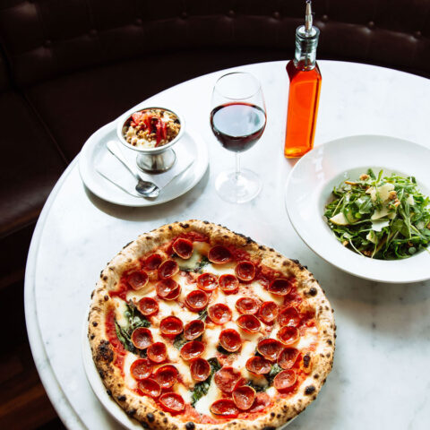 pepperoni pizza next to a salad and glass of wine