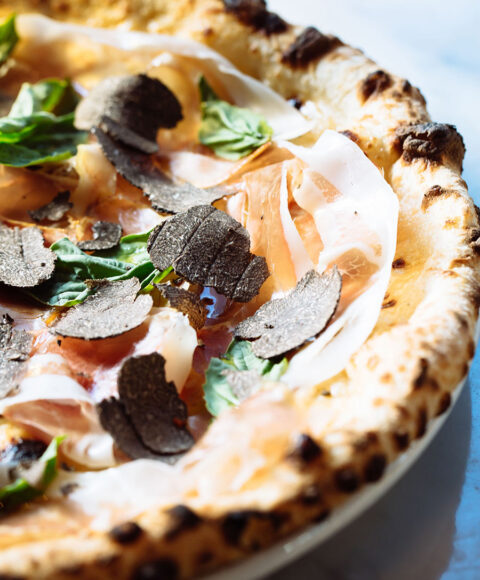 closeup of a prosciutto pizza with truffle shavings on it