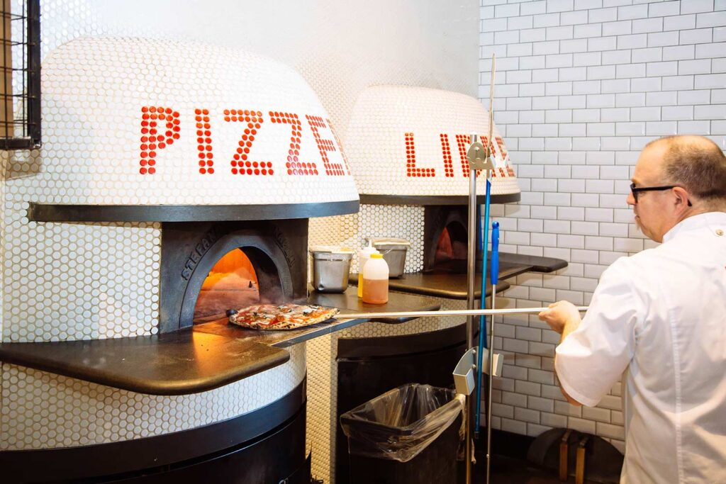 pizza chef removing a cooked pizza from a pizza oven