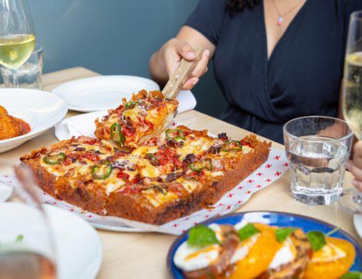 Woman taking a slice of Pizzeria Libretto's Pizza Siciliana