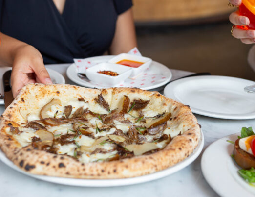 Woman on a patio taking a slice of Pizzeria Libretto's Funghi pizza