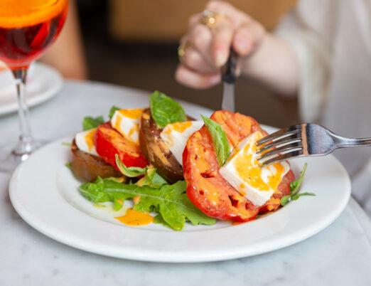 Woman in a white shirt enjoying Insalata Tomato Caprese