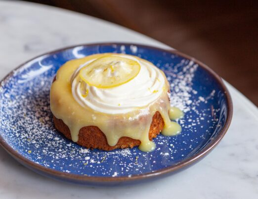 olive oil ricotta cake, lemon curd, lemon ricotta cream and candied lemon on a blue plate