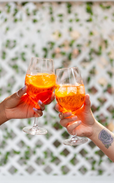 Two hands cheersing glasses of Aperol spritz at Pizzeria Libretto in Toronto