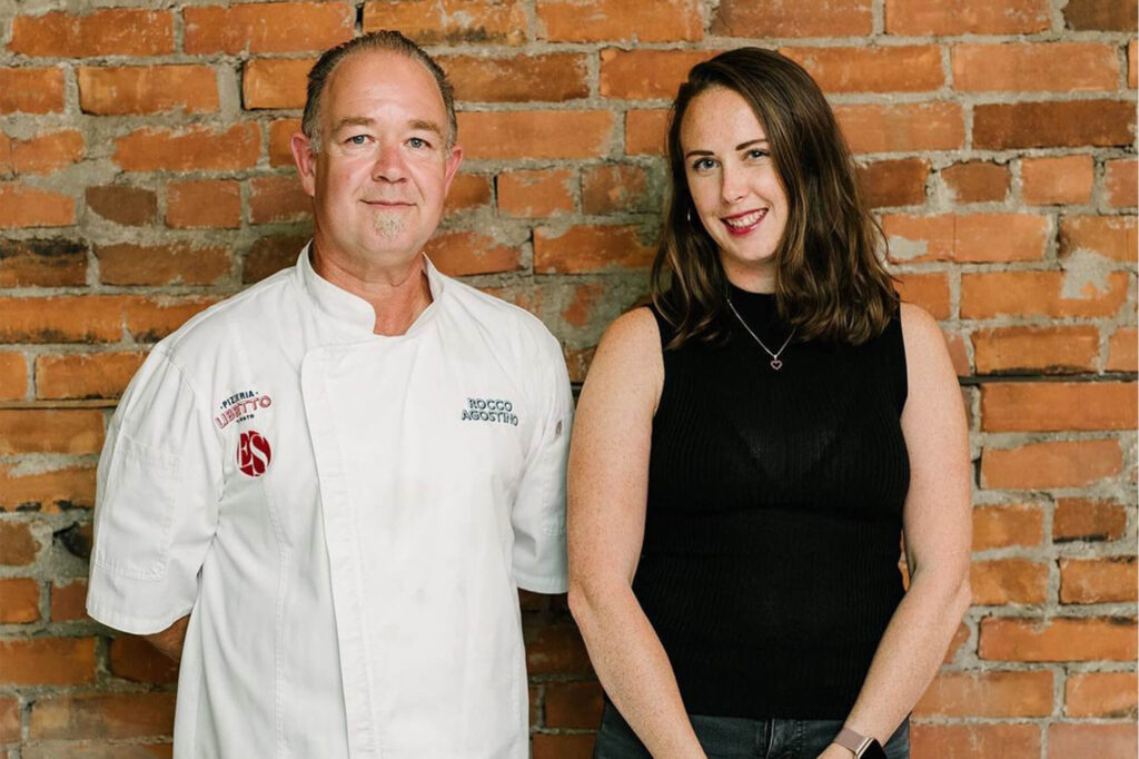 Chef Rocco and Hilary Drago standing together against a brick wall